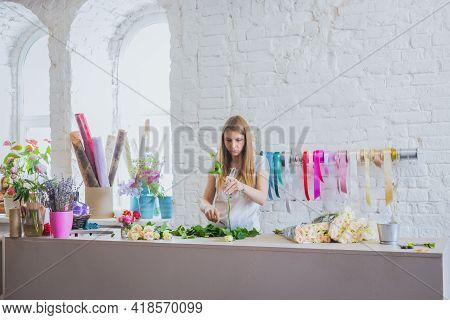 Portrait Of Professional Woman Floral Artist, Florist Cutting Flowers On Table At Flower Shop, Works