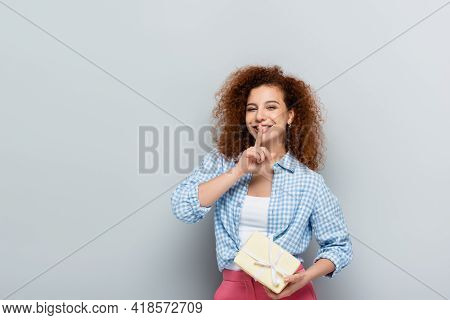 Cheerful Woman Showing Shh Gesture While Holding Gift Box On Grey Background.