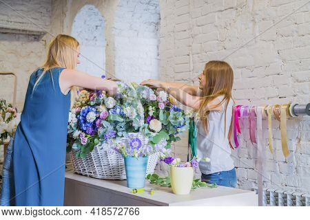 Two Professional Women Floral Artists, Florists Making Large Floral Basket With Flowers At Workshop,