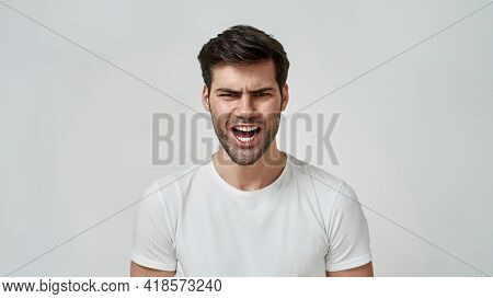 Furious, Enraged Man. Young Bearded Man Wearing T-shirt Shouting While Standing Against Grey Backgro