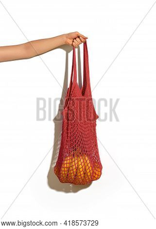 Woman Hand Holding Red String Shopping Bag With Vegetables And Fruits In Front Of White Wall. Eco Li
