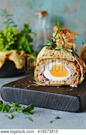 Scotch Eggs In A Pancake Bag With Greens On A Gray-blue Background. A Classic Dish In An Unconventio