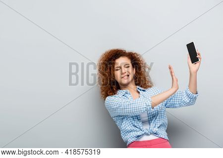 Disgusted Woman Showing Refuse Gesture Near Mobile Phone With Blank Screen On Grey Background.