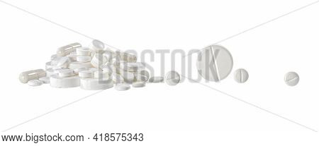 A Slide Of Different White Pills And Separately Roll Big And Small Tablets. Isolated Object On A Whi