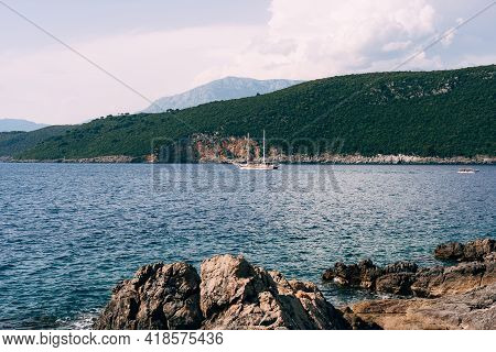 Two-masted White Yacht Sails On The Sea Along The Hilly Coast
