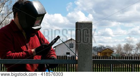 A Welder Welds Metal Using A Welding Machine. Metal Work On The Personal Plot.
