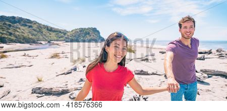 Couple tourists walking on Ship Creek beach on summer travel vacation in West Coast, South Island of New Zealand panoramic. Asian woman, Caucasian man