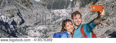 Selfie couple taking phone self-portrait on New Zealand by Franz Josef Glacier. New Zealand tourists smiling happy in nature in Westland Tai Poutini National Park. Horizontal banner landscape.