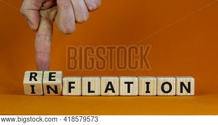 Inflation Or Reflation Symbol. Businessman Turns Cubes And Changes The Word Inflation To Reflation.