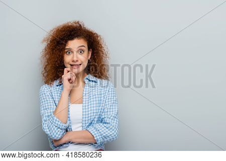 Discouraged Woman Holding Hand Near Face While Looking At Camera On Grey Background.