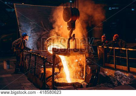 Pouring Bright Liquid Iron Or Metal With Sparks Into Container In Steel Mill Or Workshop Blast Furna