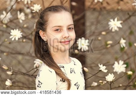 Child With Blossoming Flowers Outdoor. Little Girl On Floral Blossom In Spring. Beauty Kid With Fres