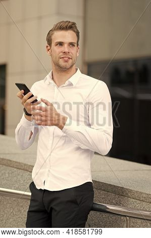 Man Checking Emails In Morning Urban Background. Businessman Send Messages Or Texting With Smartphon