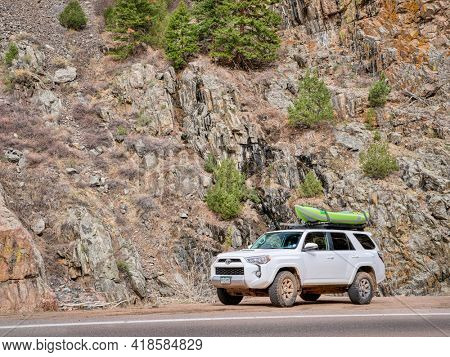Fort Collins, CO, USA - April 26, 2021 : Toyota 4 Runner SUV (2016 Trail Edition) with a whitewater inflatable kayak (Aire Force) in the Poudre River Canyon, early spring scenery.