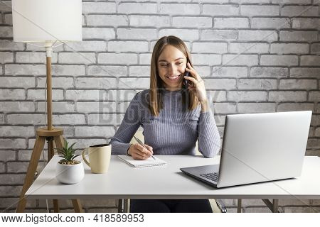 Adult Woman Sit At Desk In Living Room Study On Laptop Making Notes, Happy Young Woman Work On Compu