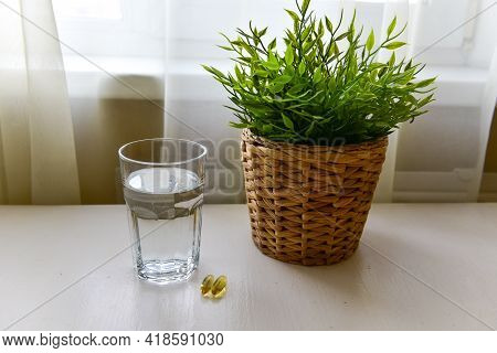 Omega-3, Spirulina, Chlorophyll Capsules And Glass Of Water On White Wooden Table. Dietary Supplemen