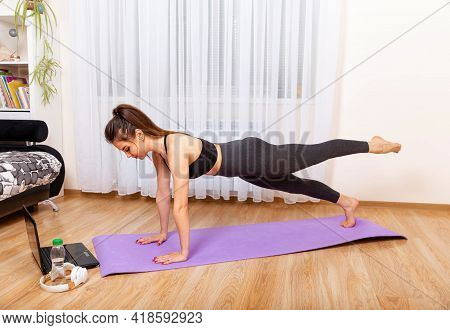 Peaceful Woman Stretching Body Indoors. Woman Working Out At Home. Fit Woman Doing Yoga Plank And Wa