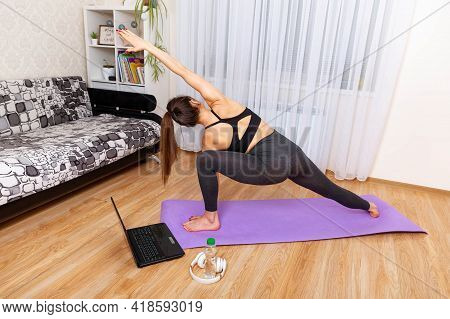 Beautiful Woman Practicing Yoga At Home With Laptop. Young Woman Workout, Practicing Yoga In Room, R