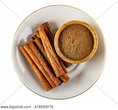 Cinnamon Sticks And Bamboo Bowl With Ground Cinnamon In White Saucer Isolated On White Background. T