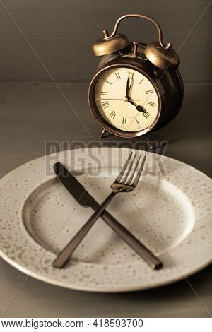 concept of intermittent fasting, ketogenic diet, weight loss. fork and knife on plate, alarmclock