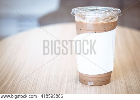 A Glass Of Iced Mocha Drink Wrapped By White Tissue Paper On The Table