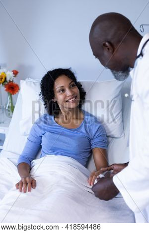 African american male doctor putting oximeter on finger of smiling female patient in hospital bed. medicine, health and healthcare services.