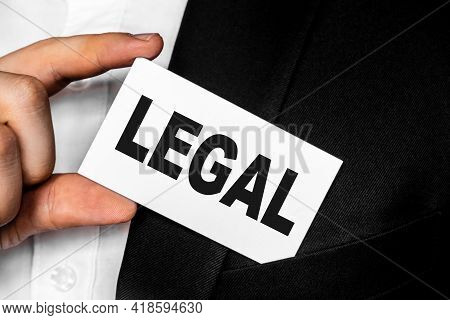 Inscription Legal On A White Business Card. A Man In A Black Business Suit Lowers Or Removes From Hi