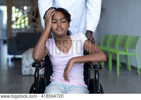 African american male doctor pushing sick mixed race girl in wheelchair through hospital corridor. medicine, health and healthcare services.