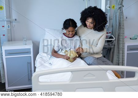Mixed race mother comforting her sick daughter holding teddy bear in hospital bed. medicine, health and healthcare services.
