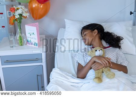 Sick mixed race girl holding teddy bear lying asleep in bed in a hospital ward. medicine, health and healthcare services.