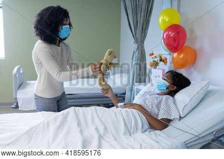 Mixed race mother and sick daughter in face masks in hospital, playing with teddy bear. medicine, health and healthcare services during covid 19 coronavirus pandemic.