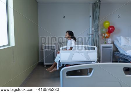 Bored sick mixed race girl sitting on hospital bed looking out of window. medicine, health and healthcare services.