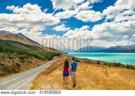 New Zealand travel - couple tourists looking at nature view of Aoraki aka Mount Cook at Peter's lookout, a famous tourist destination on New Zealand Road Trip vacation.