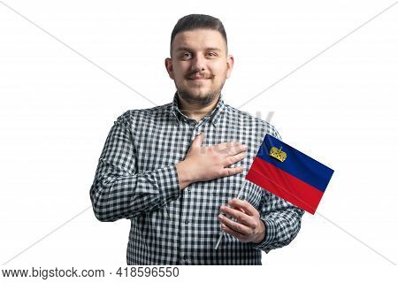 White Guy Holding A Flag Of Liechtenstein And Holds His Hand On His Heart Isolated On A White Backgr