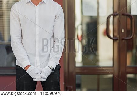 Male Waiter In Protective Gloves Standing Near Restaurant Front Door Informing About Takeaway Servic