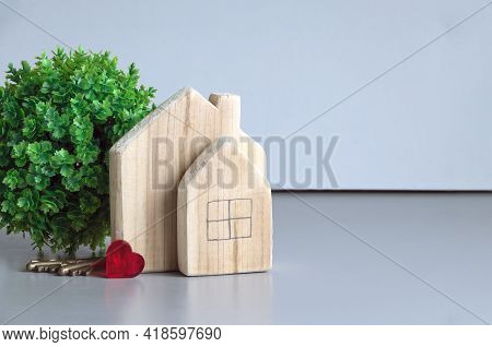 A Green Plant, Wooden Houses, Keys And A Red Heart On A Gray Background. The Concept Of Love In The