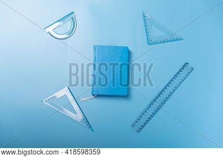 A Variety Of Rulers And A Notebook. Blue Rulers And Blue Notepad On A Blue Background. Top.