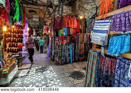 JERUSALEM, ISRAEL - JULY 16, 2018: Colorful traditional clothes for sale at the famous bazaar in old city of Jerusalem - popular place and tourist destination.