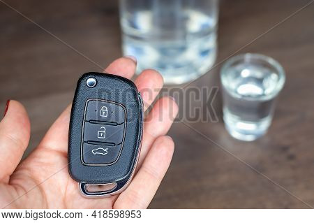 Close-up Of Car Key In Woman Hand On The Background Of Shot Glass Of Vodka With Bottle Of Alcohol