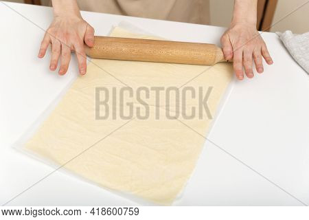 Cook Rolls Out The Dough Thinly With Rolling Pin. Process Of Preparing The Dough For Baking