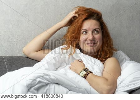 Charming Young Woman With Ginger Hair Lying Under White Cover. Playful Gaze.