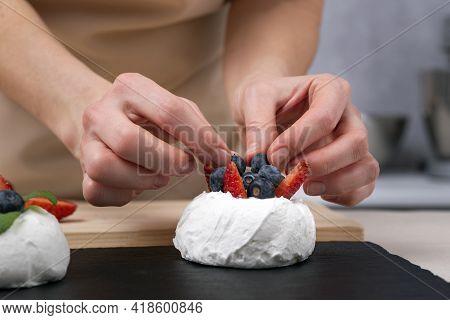 Pastry Chef Decorates Cake With Fresh Strawberries And Blueberries. Cake Anna Pavlova.