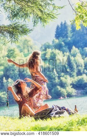 Pair Of Hippie Girls By A Lake Are Relaxing