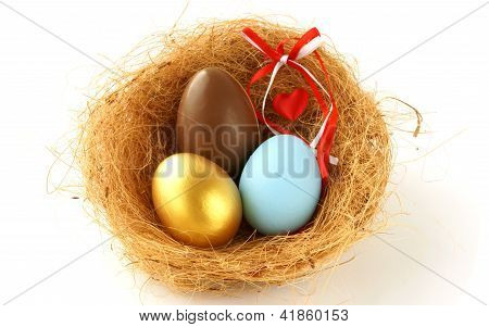 Gold, Chocolate And Blue Eggs In The Nest