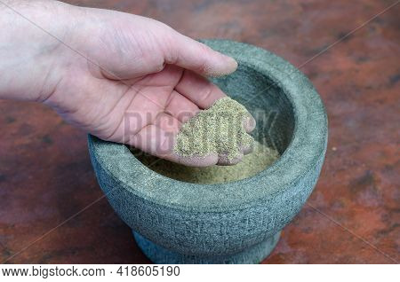 A Man Checks The Quality Of Grinding Spices And Herbs In A Gray Stone Mortar. Hand With A Mixture Of