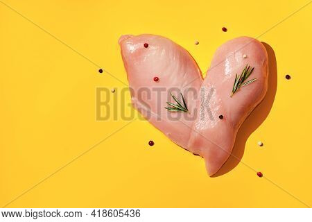 Fresh Chicken Breast With And Herbs On Yellow Background. Heart Shaped Chicken Fillet. Preparation F