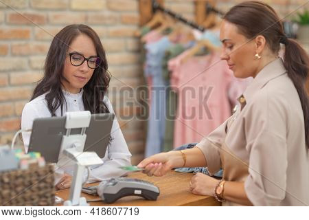 Shop Assistant Looks At The Computer Monitor As She Accepts The Contactless Payment By A Female Cust