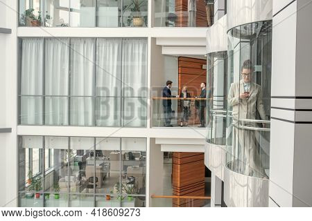 Busy people working in business hall: three colleagues discussing project, young woman checking phone in glassy elevator