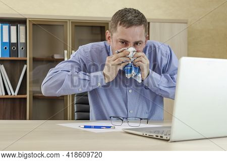 Mature Businessman At Office Desk Blowing His Nose. A Cold Office Worker Blows His Nose Into A Handk
