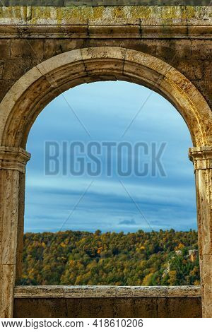 Overview arch. The central square of tufa city of Sorano. Italy, southern Tuscany. Steep mountain slope overgrown with autumn forest. The concept of active, historical and photo tourism